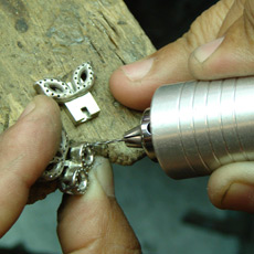 Jeweler drilling holes for diamonds in clasp
